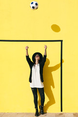 Alternative woman playing with soccer ball in front of a yellow wall