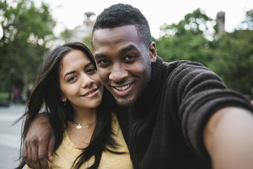 Black young couple taking a selfie in the city