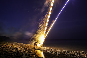 Man lighting fireworks at night