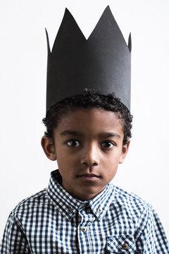 Portrait of a boy wearing a black crown