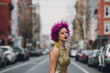Young woman in a party dress standing in the street