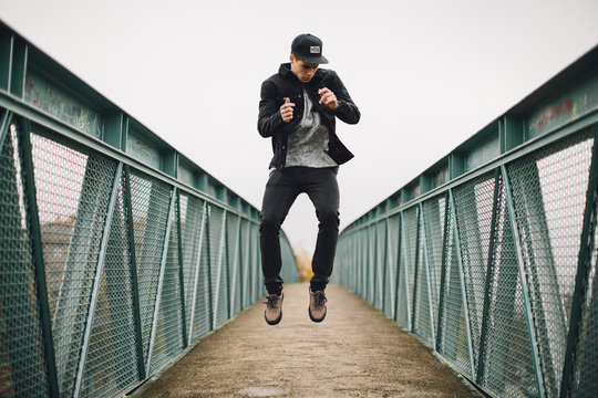 Cool young man jumping on a bridge