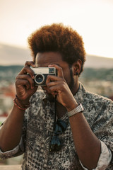 Young black man taking a photo with an old camera at sunset