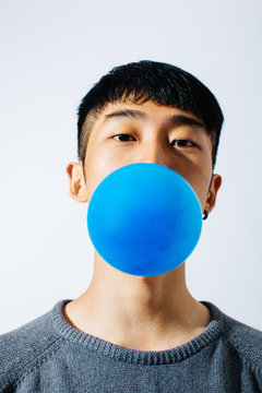 Asian man blowing a blue balloon over white background
