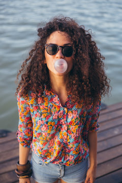 Girl with curly hair blowing a bubble with pink bubblegum
