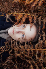 A pale woman with blue eyes lies in golden ferns