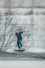 Teenager is doing a trick with his longboard