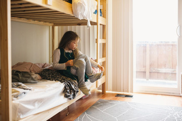 Young girl sitting on bed getting clothes on