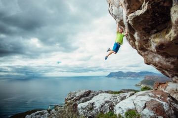 Young man rock climbing on an overhanging cliff