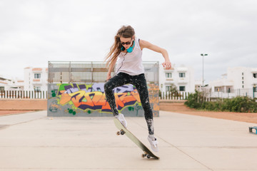 Woman Jumping With a Skateboard in a Skate Park