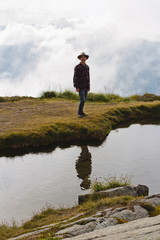 young man stands by water on mountain