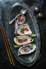 Oysters served on ornate metal platter with garnish Seen from above