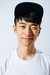 Portrait of young asian man winking in a cap over white background