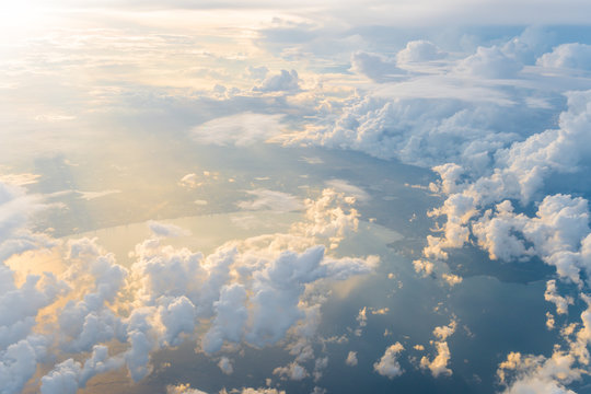 White clouds and blue sky at sunrise, view from above air plane window.