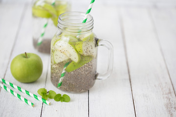 Apple green sliced with chia seeds in glass and fresh apples on the wooden table, Drink to good health