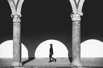 Fashion woman walking through Italian architecture