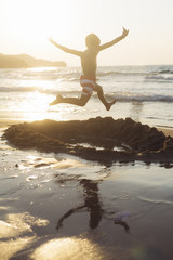 Child jumping at sunset by the sea