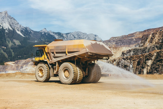 huge yellow quarry truck watering the dry road in a construction area