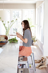 Woman holding herbs at kitchen counter with pet dog on floor