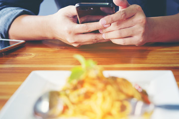 Close-up Man's hands use pointing finger Mobile smart Phone on Food table, technology and home concept
