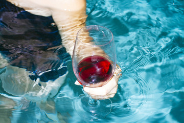 young woman holds wine in pool