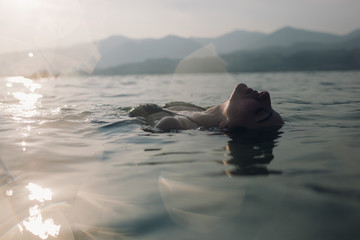 Young woman floating in lake at sunset