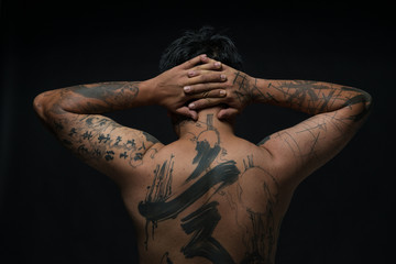 Rear view studio shot of tattooed young man with hands behind head