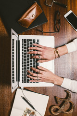 Woman's hands working on wooden workspace