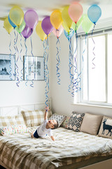 Little boy playing with balloons on bed
