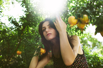 Eve like young Mediterranean woman in garden with fruit