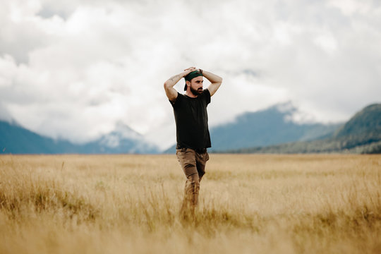 A weary man stands alone in the middle of a New Zealand meadow