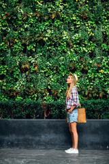 Beautiful Woman Standing by a Tropical Plant Wall