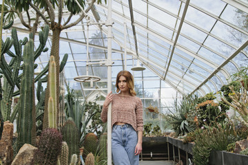 Young woman stands in conservatory