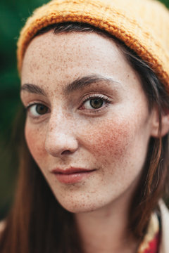 Portrait of young freckled woman with yellow bonnet