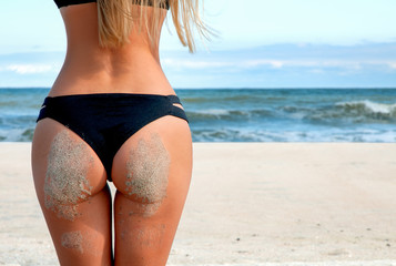 Sandy woman buttocks on the beach. Sexy tanned body.