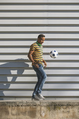 Black man playing with soccer ball on cityscape