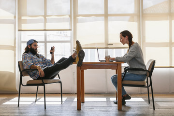 Hipster man using mobile phone while young woman studying with laptop in a room