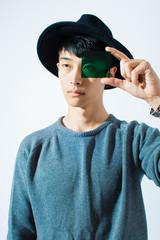 Portrait of an asian man holding a green glass