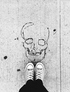 Skull printed on the asphalt and feet
