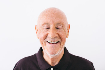 Portrait of an elderly man laughing with eyes closed over white