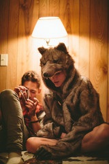 A boy and girl in a wolf costume sit on a bed together as he reads and she listens
