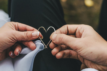 bridal couple holding two fishing hooks together forming a heart