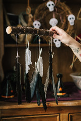 Woman holding feather mobile in front of witches altar
