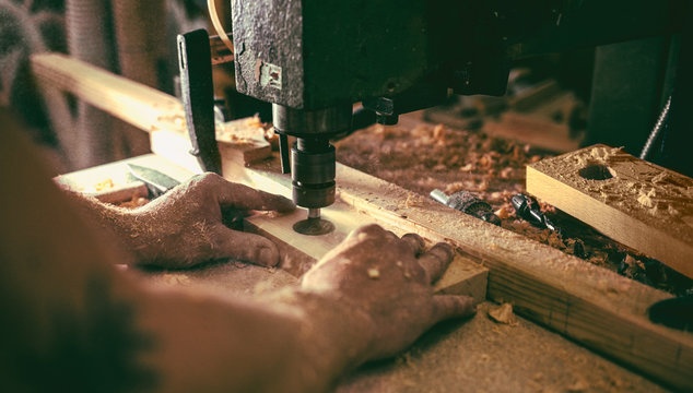Carpenter Drilling a Hole