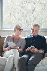 Mature couple with grey hair looking at digital tablet and phone at home