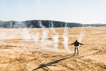 A lone man releases smoke in the desert