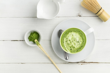 Matcha latte cup on white background top view. This latte is a delicious way to enjoy the energy boost & healthy benefits of matcha. Matcha is a powder of green tea leaves packed with antioxidants.
