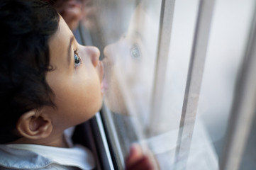 Cute baby girl kissing glass window pane