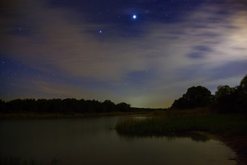 Bright stars in the night sky with clouds on a background of the river.