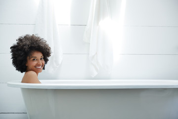 African American woman relaxing in bathtub